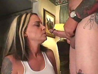 sweet woman licking the cock of a tattooed